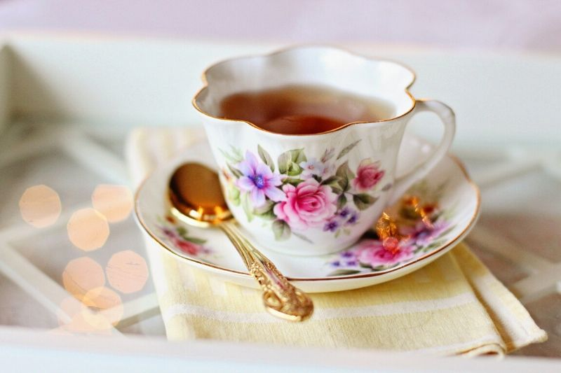 A teacup with a floral vintage print on a saucer