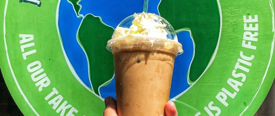 A hand holds an iced bounty drink with whipped cream on top