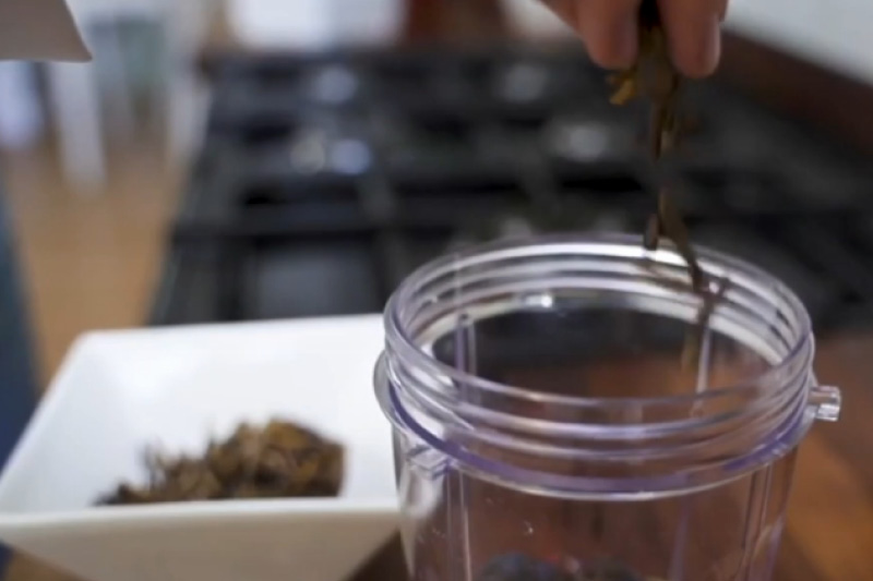 A hand sprinkles mealworms into a jar ready to make the smoothie