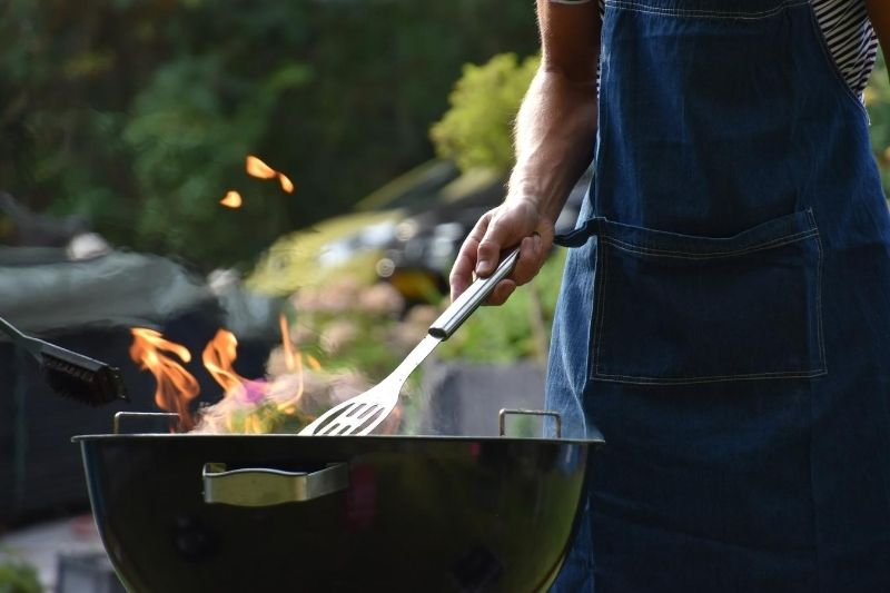 A person cooking on a kettle barbecue in the sunshine