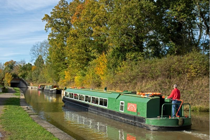 A green and red canal boat travelling on the Wey and Arun Canal on a sunny day
