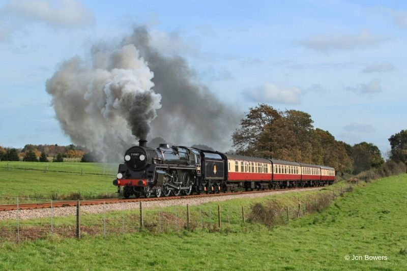 The red Bluebell Railway train steams through the countryside